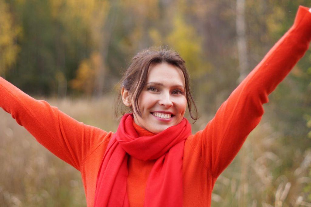 femme écartant les bras avec une écharpe rouge afin d'être toujours positive pour gérer son stress