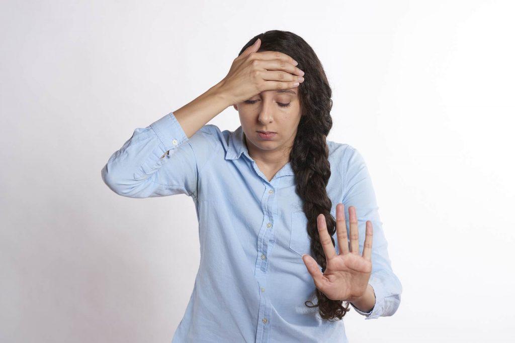 femme qui dit stop avec sa main gauche afin de repousser son anxiété pour gérer son stress